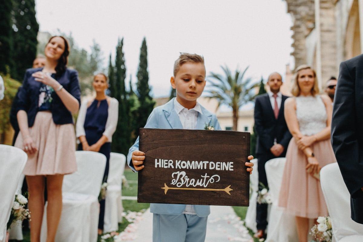 Ein kleiner Junge mit dem Schild: Hier kommt Deine Braut läuft vorraus.