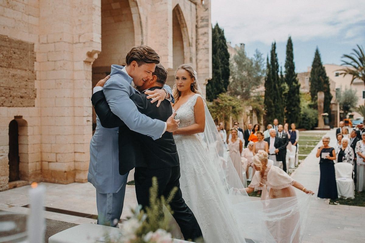 Der Bräutigam umarmt herzlich den Vater der Braut bei der Übergabe.