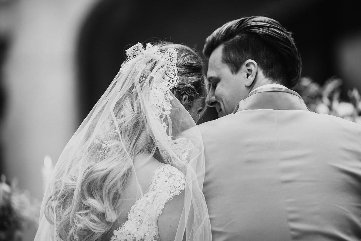 Blick von hinten auf das Brautpaar welches sich während sie der Sängerin zuhören aneinander schmiegt.