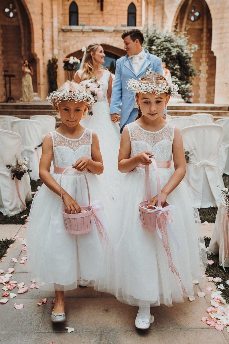 Der Auszug vom Brautpaar. Vor ihnen laufen die Blumenmädchen und streuen Rosenblätter.