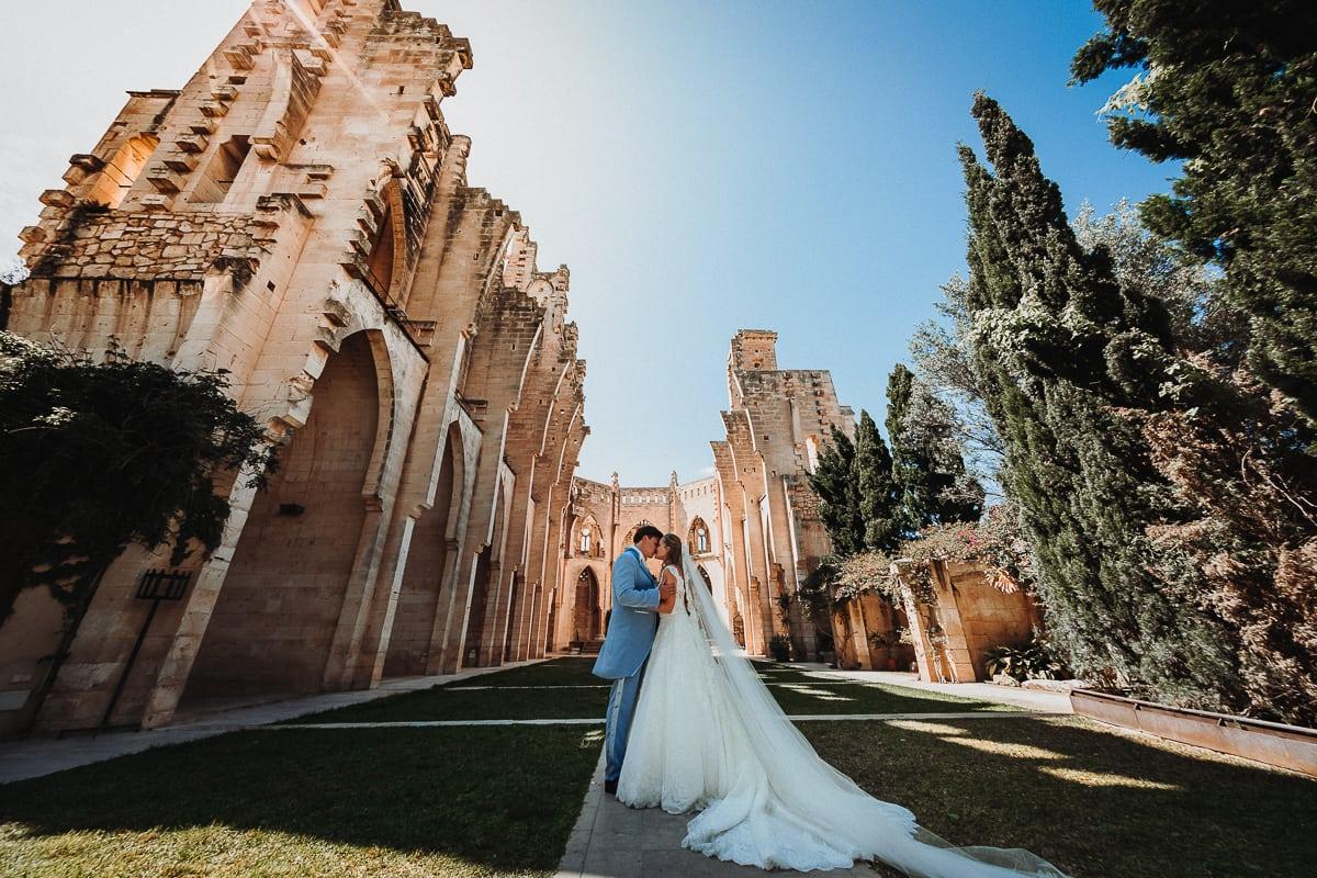 Beeindruckende Super Weitwinkelaufnahme des sich küssenden Brautpaares vor der imposanten dachlosen Kirche Iglesia Nova auf Mallorca.