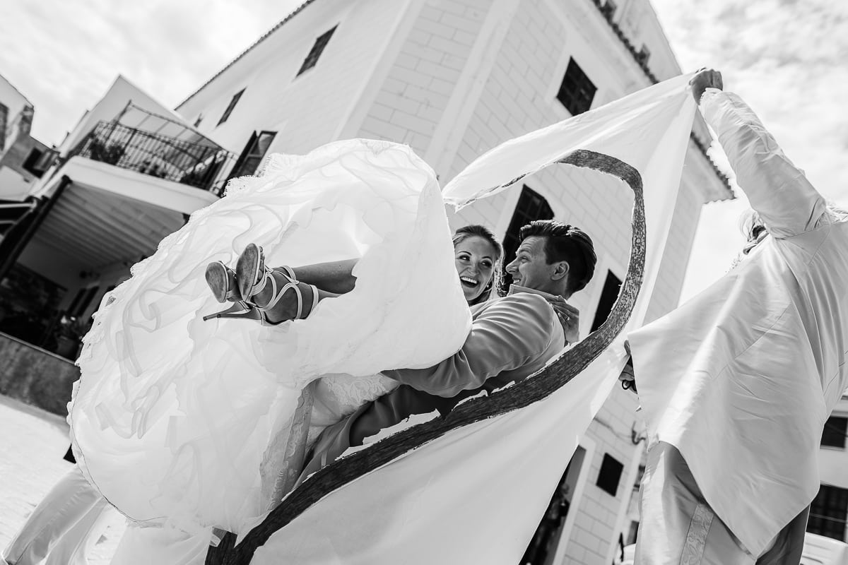 Der Bräutigam trägt seine Braut durch das ausgeschnittene Herz hindurch.