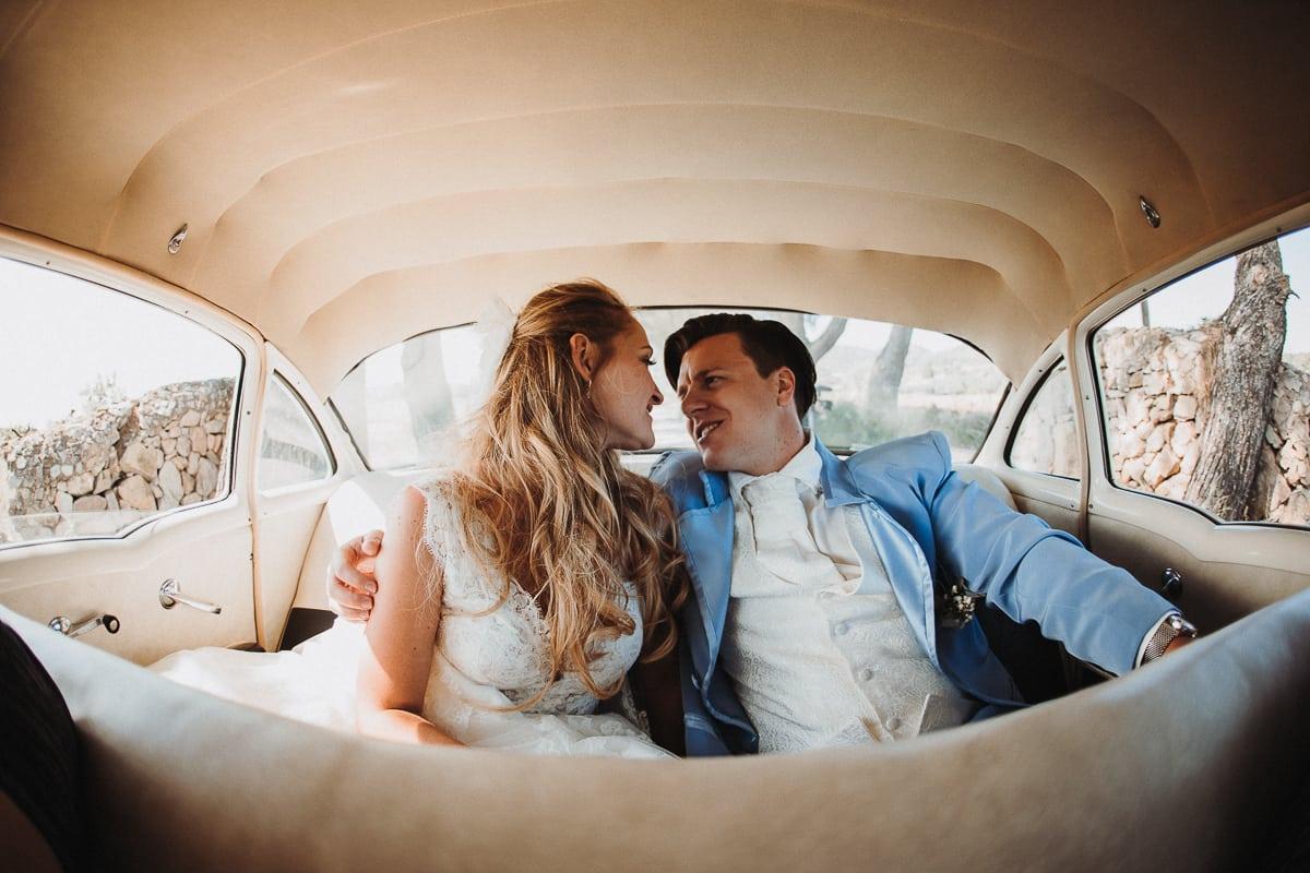 Das verliebte Brautpaar während der Fahrt in ihrem Hochzeitsauto.