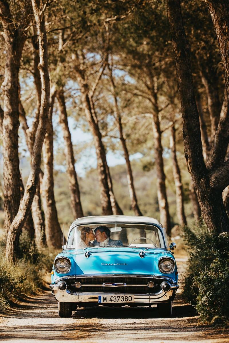 Der Hochzeitsoldtimer inmitten einer Pinienallee mit dem sich küssenden Brautpaar im Auto.