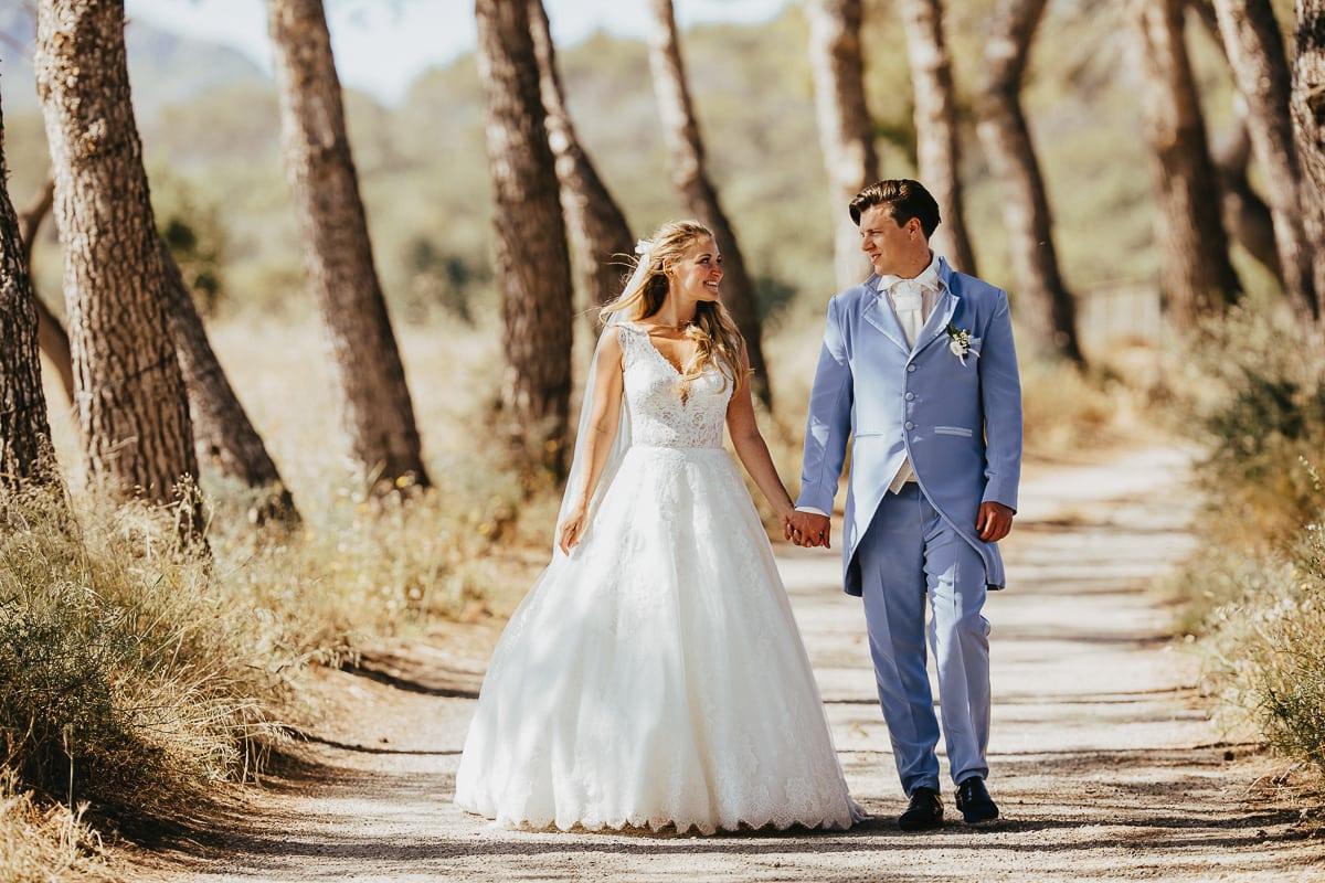Das Brautpaar spaziert Hand in Hand durch die Pinienalle nahe bei Son Servera.