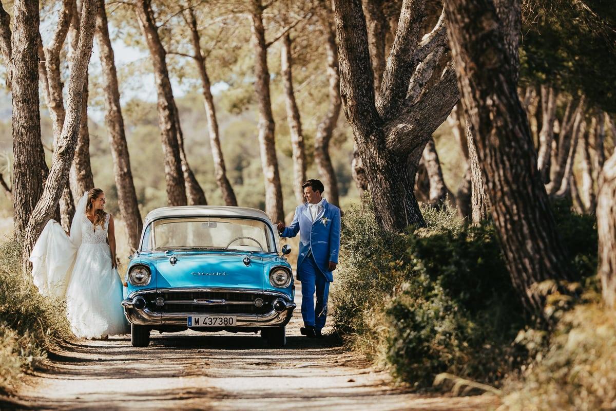 Das Brautpaar spaziert jeweils links und rechts vom Hochzeitsauto den Weg entlang.