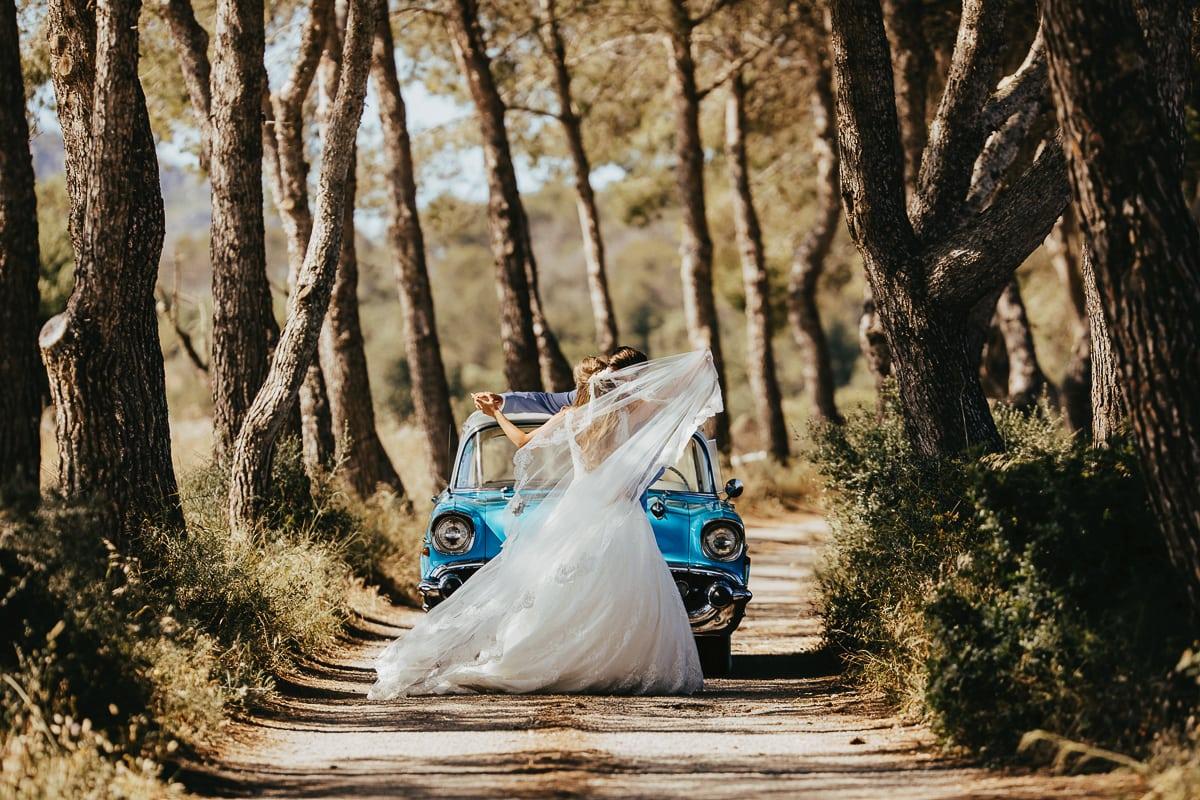 Das Brautpaar tanzt vor dem Oldtimer in der Natur.