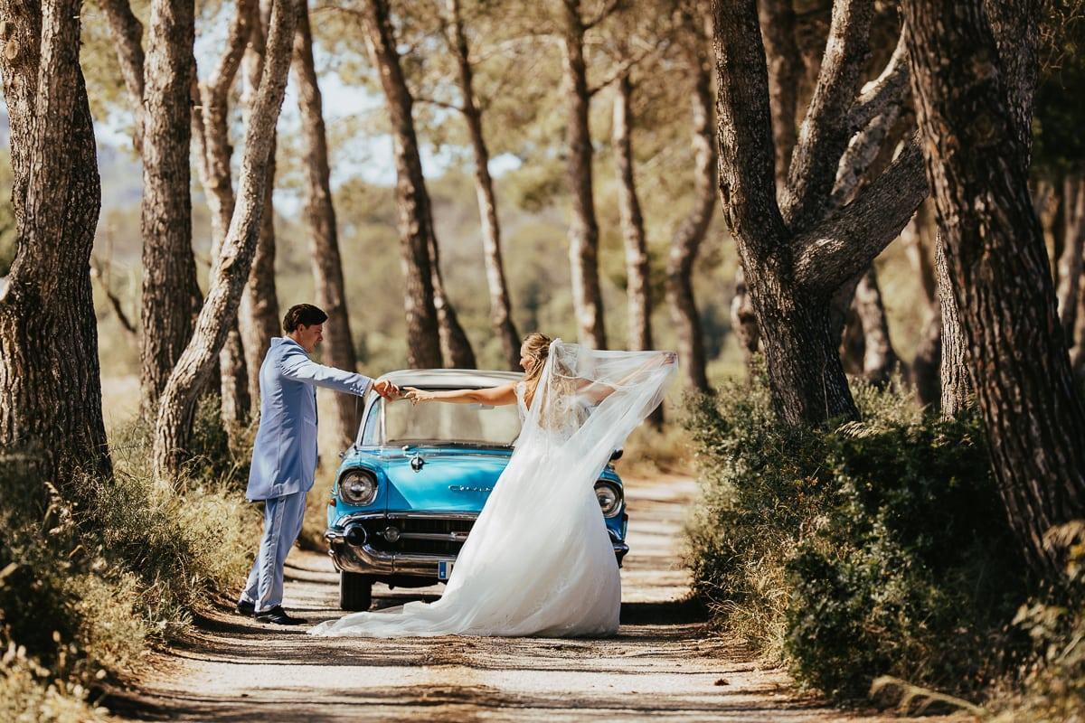 Momentaufnahme des glücklich schwelgenden Brautpaares auf einem weg im grünen mit ihrem Hochzeitsauto.