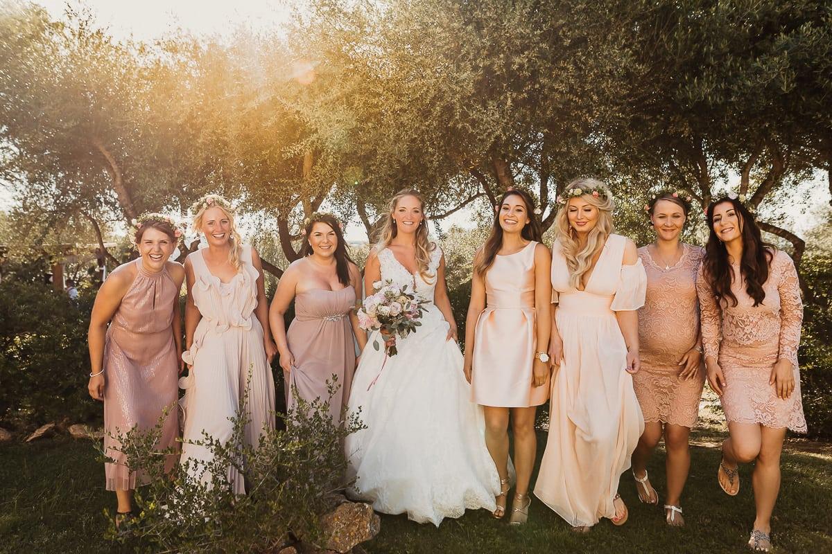 Lebhaftes Gruppenfoto der Braut mit ihren Mädels im zauberhaften Gegenlicht.