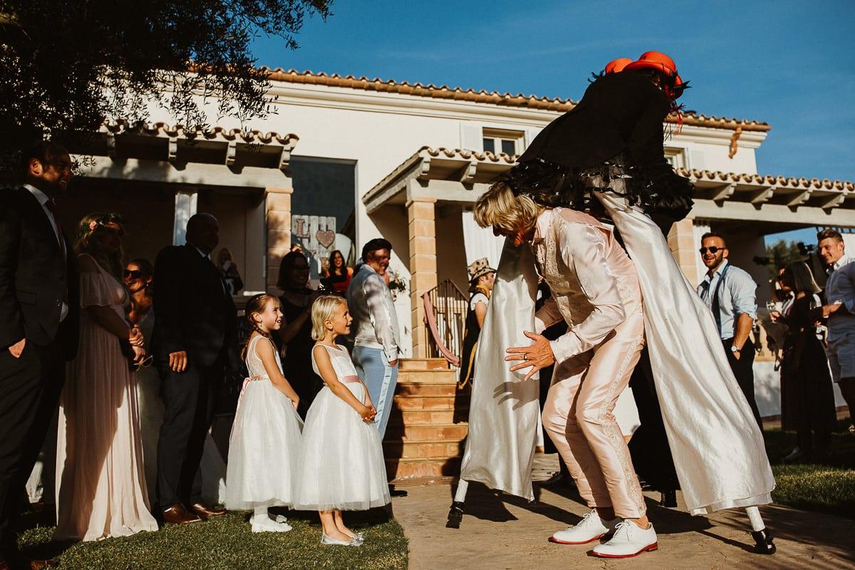 Der Vater des Bräutigams geht lachend durch die Unterhaltungskünstler auf Stelzen hindurch.