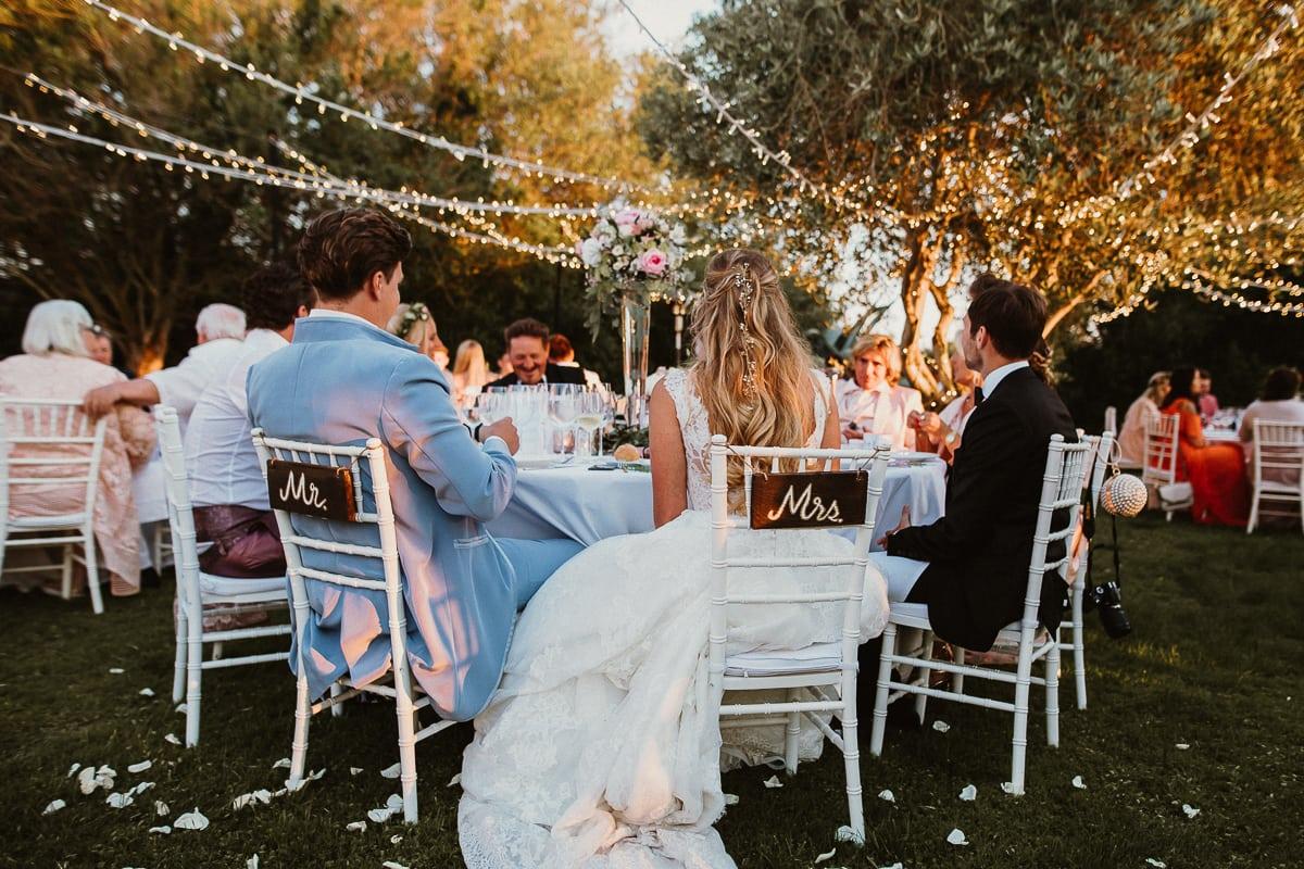 Das Brautpaar von hintem im Abendlicht an ihrem Hochzeitstisch sitzend.