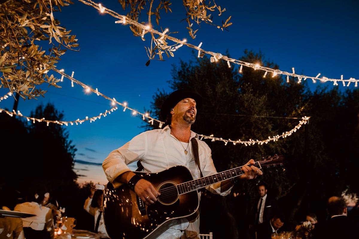 Ein Sänger mit Gitarre begleitet die Gäste während des Hochzeitsdinners.