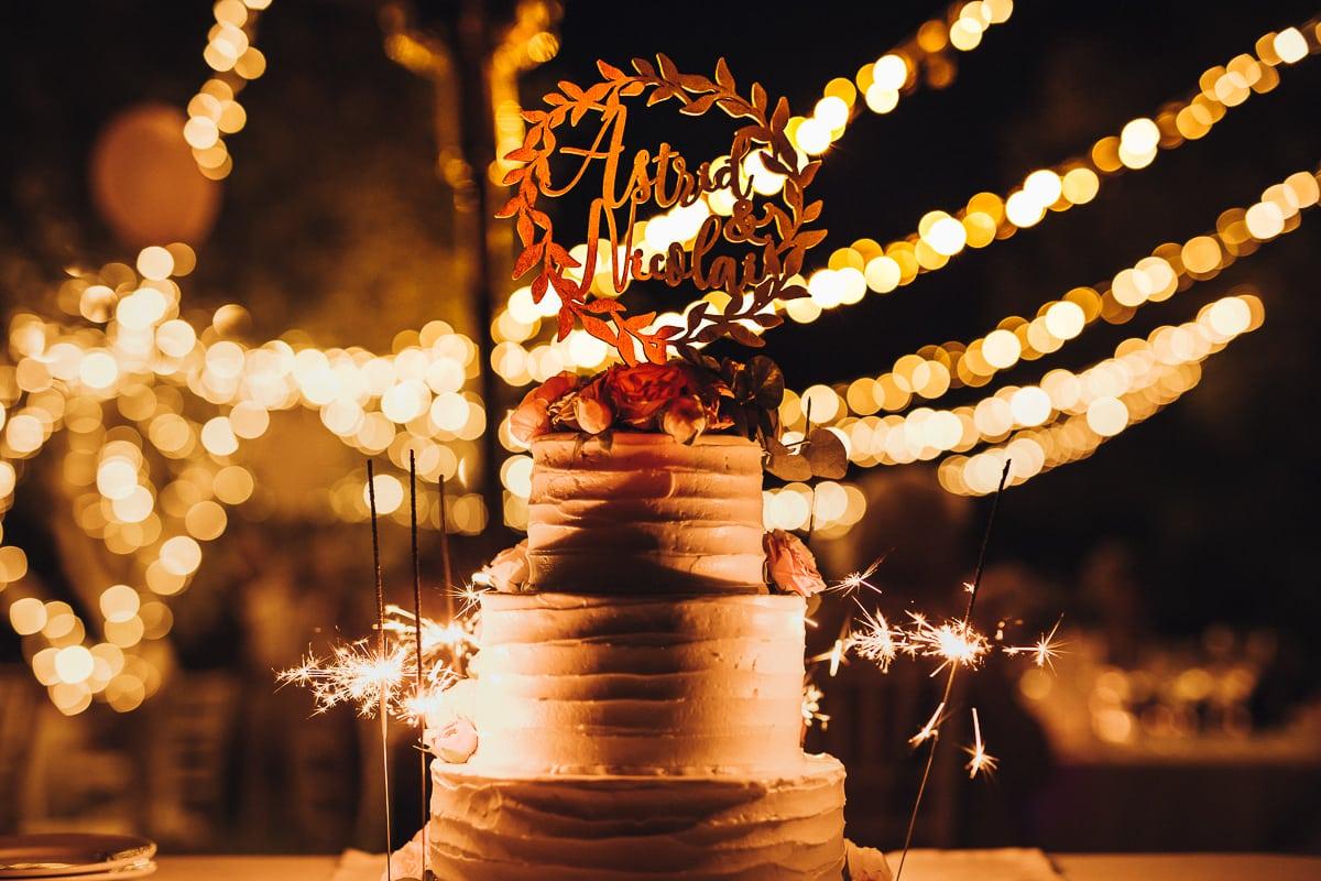 Die Hochzeitstorte vor Lichterketten mit brennenden Wunderkerzen.
