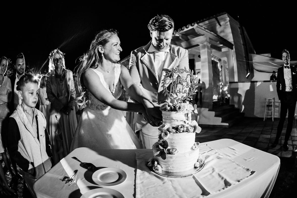Das lachende Brautpaar beim Anschneiden der Hochzeitstorte.