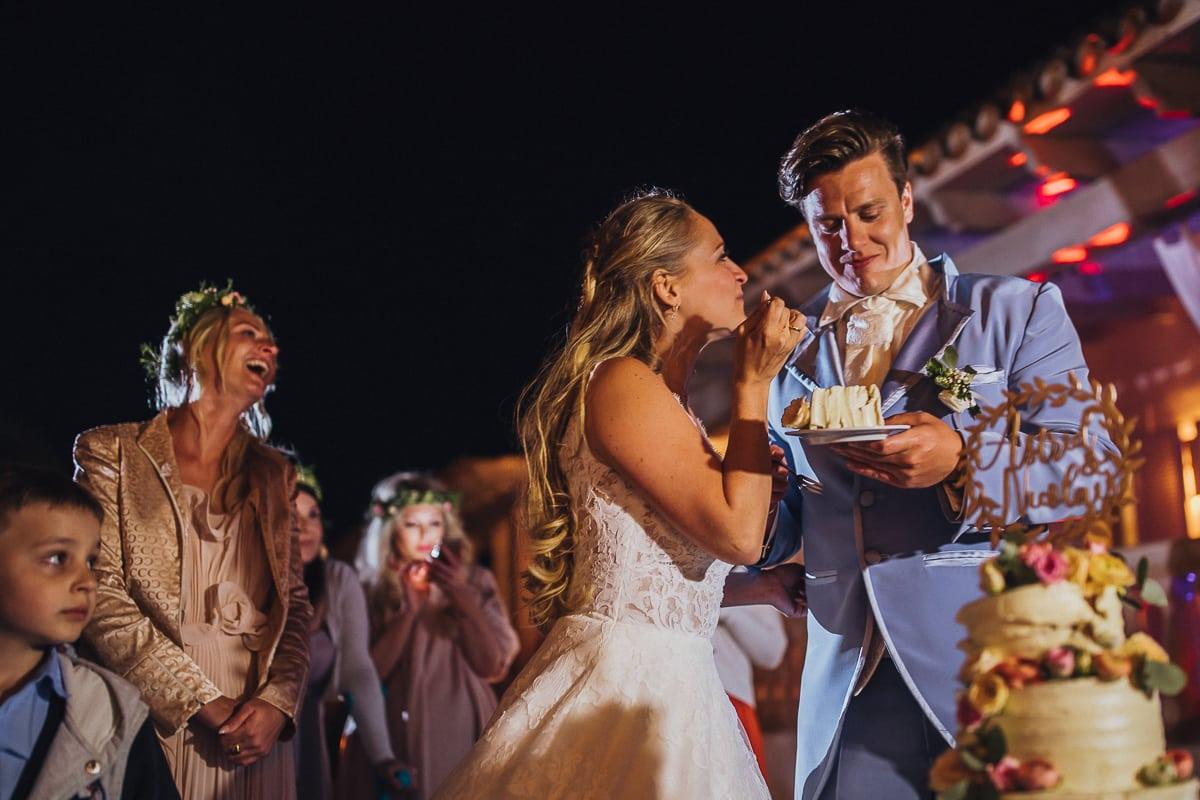 Das lächelnde Brautpaar beim Kosten der Hochzeitstorte.