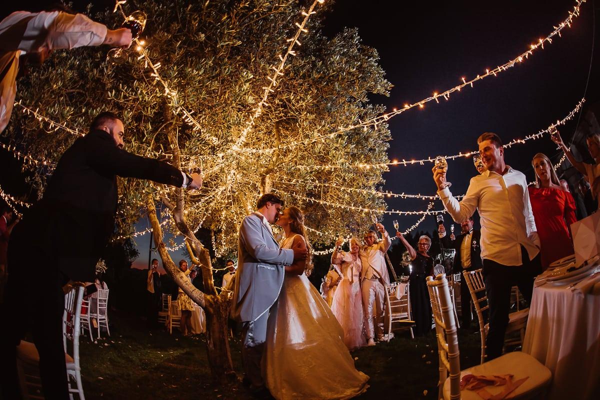 Das Brautpaar küsst sich unter den romantischen Lichterketten umringt mit der Jochzeitsgesellschaft welche die Gläser heben.