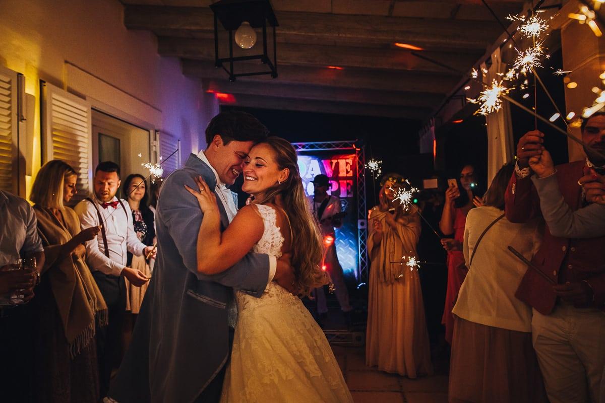 Das frisch vermählte Hochzeitspaar tanzt umringt von seinen Gästen und Wunderkerzen.