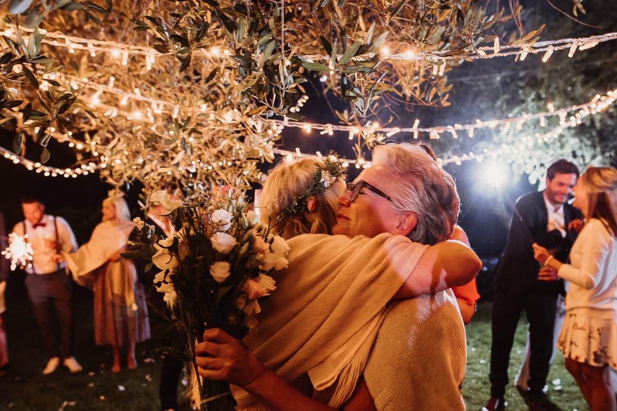 Die Brautmutter wird mit ihrem Geburtstagsblumenstrauss in der Hand umarmt.
