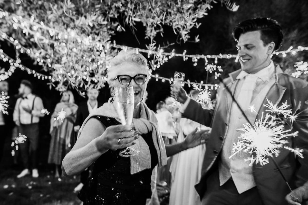 Die Brautmutter überglücklich lachend mit einem Champangerglas in der Hand und dem Schwiegersohn an ihrer Seite.