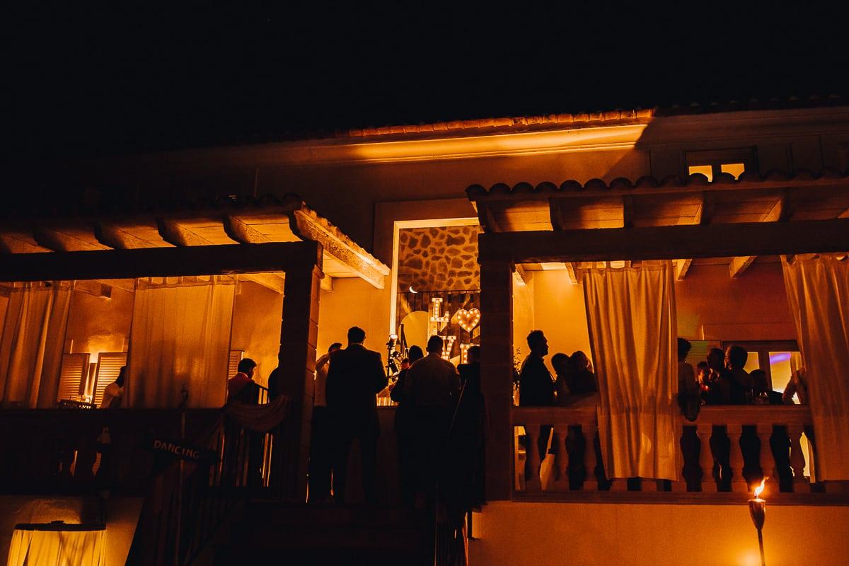 Die Hochzeitsparty Terasse in der Abendbeleuchtung und Silhouetten der Gäste.