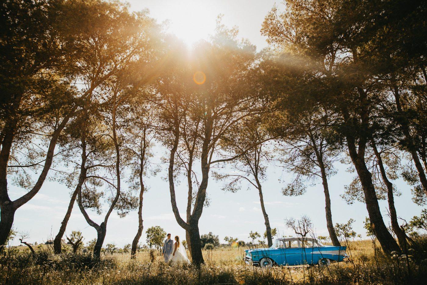 Das Hochzeitspaar in der Natur Mallorcas mit einem blauen Oldtimer als Hochzeitsauto