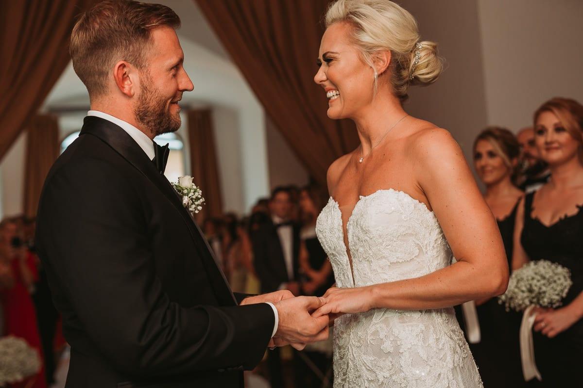 Die Braut lächelt Ihren Bräutigam verliebt an nachdem er ihr den Ring angesteckt hat.