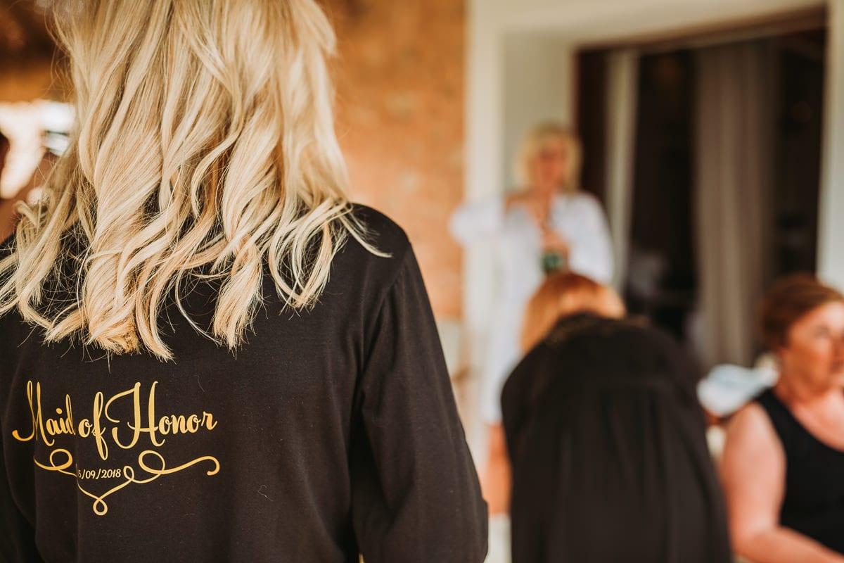 Eine der Trauzeuginnen von hinten mit dem goldenen Schriftzug Maid of Honor auf dem schwarzen Morgenmantel.