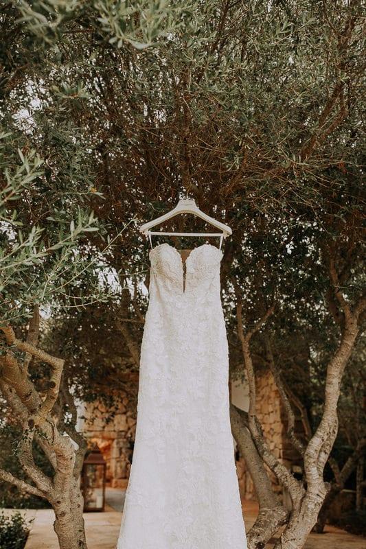 Brautkleid hängt am Olivenbaum.