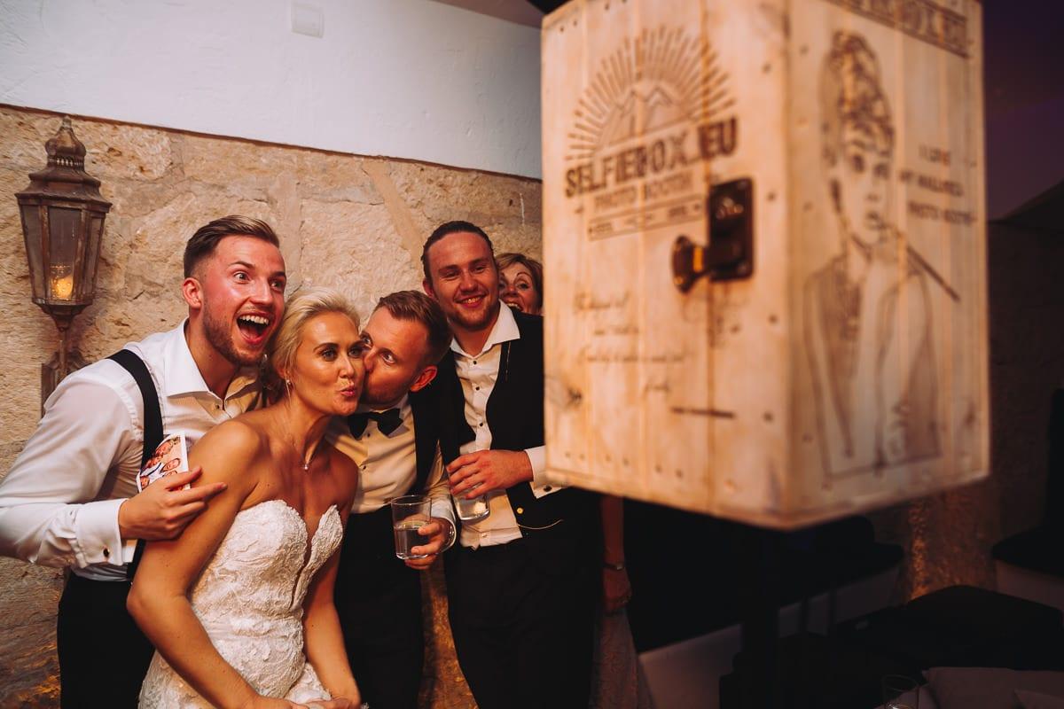 Der Bräutigam küsst die Braut vor der Selfiebox, dem photo booth.