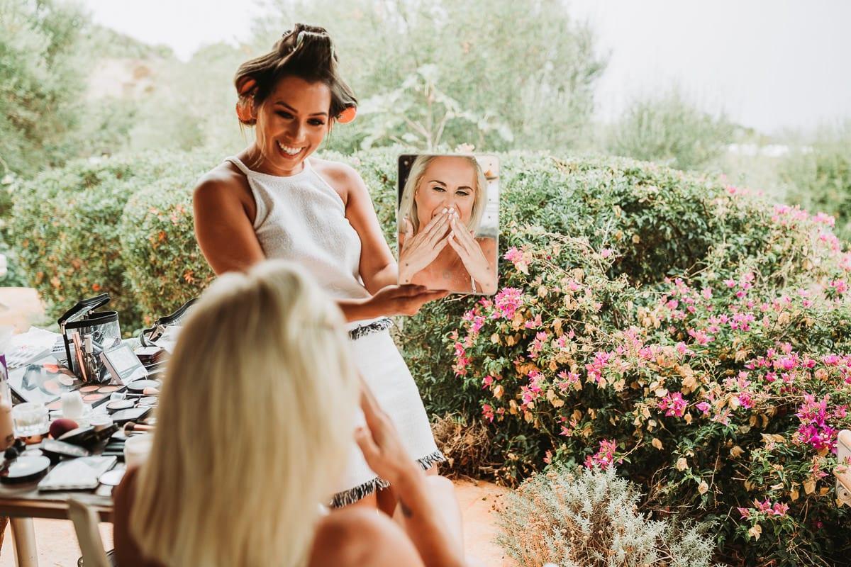 Die Braut ist ergriffen als sie sich im Spiegel fertig geschminkt sieht.
