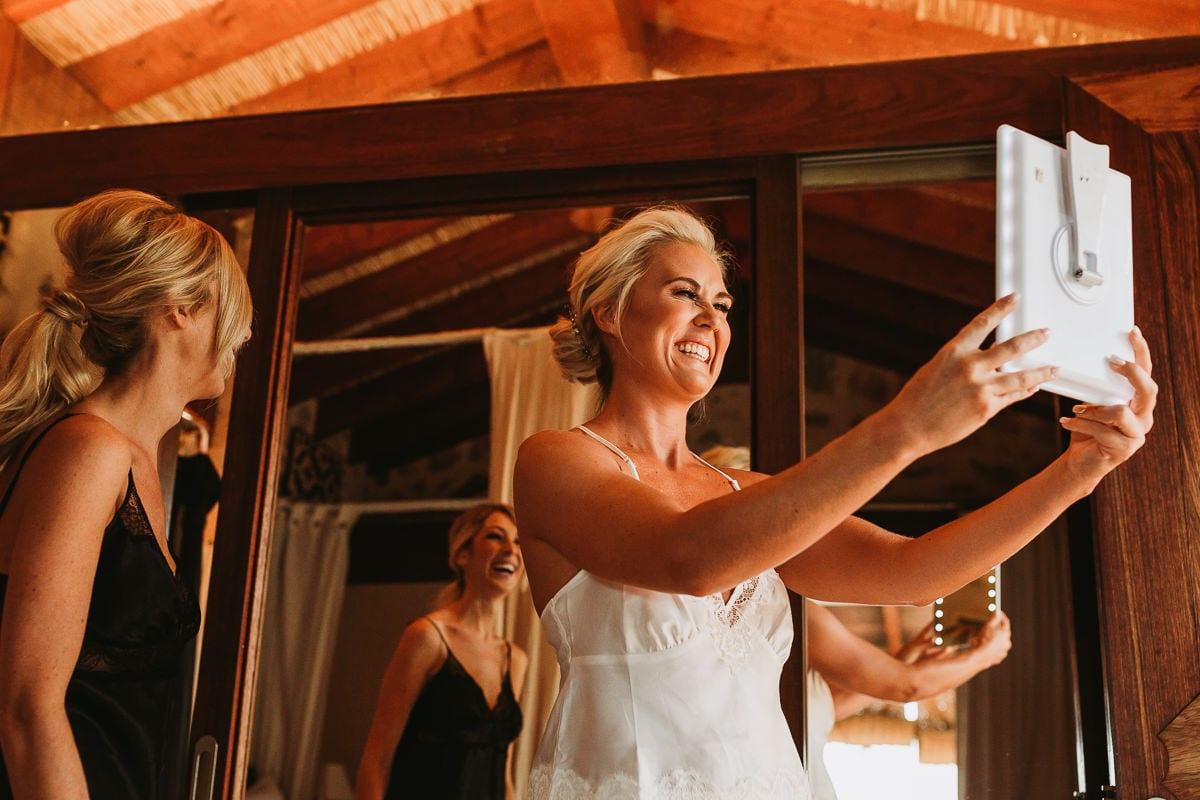 Die Braut schaut in den Spiegel und freut sich riesig über ihre Frisur.