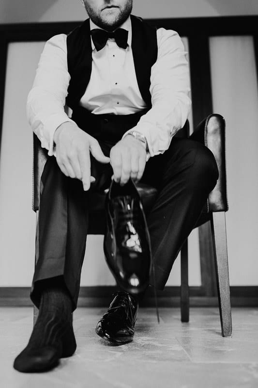 Der Bräutigam zieht seine Schuhe an.