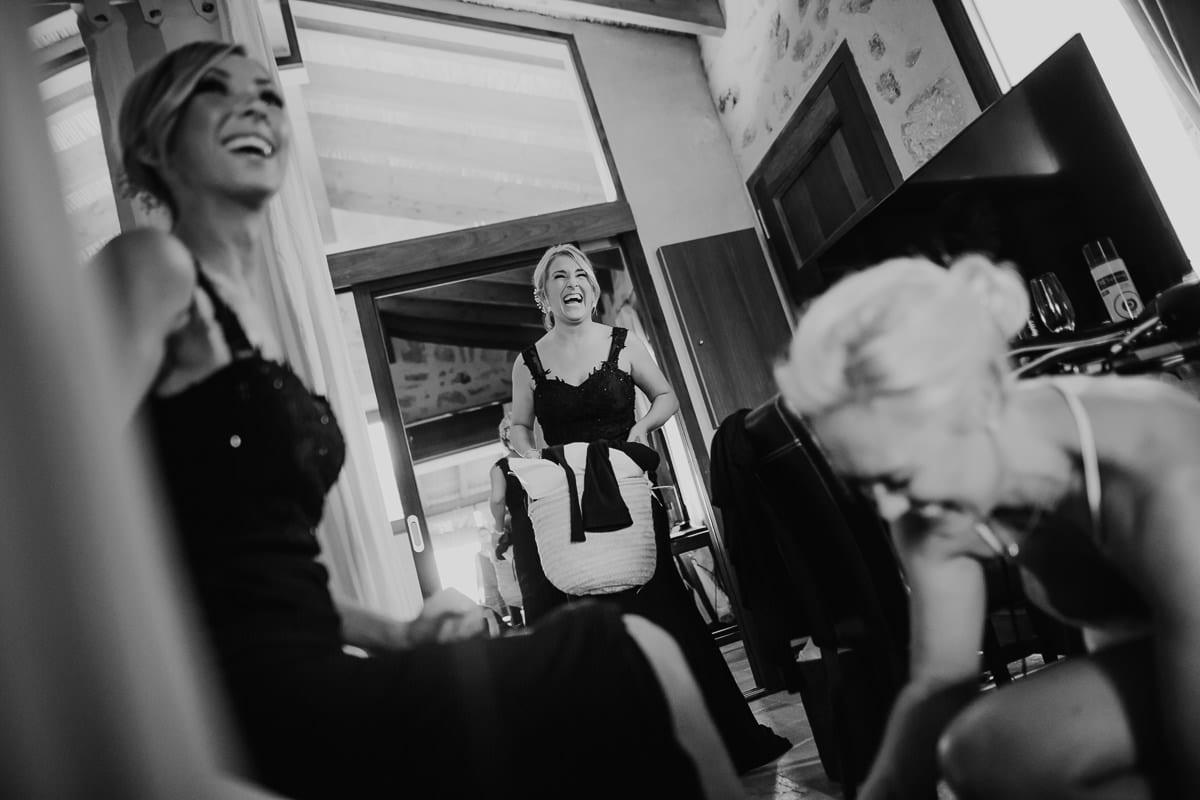 Alle lachen herzlich als die Braut ihrer Schwester hilft die Schuhe anzuziehen.