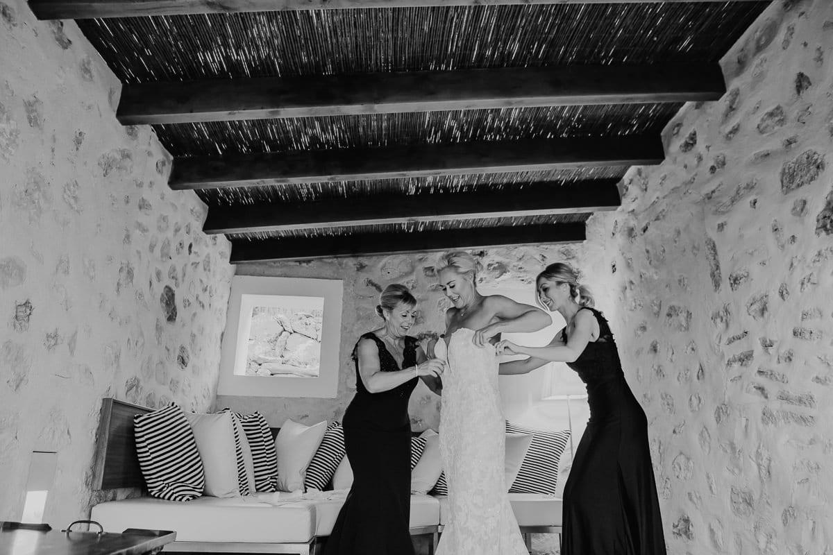 Die Braut bekommt ihr Kleid angezogen.