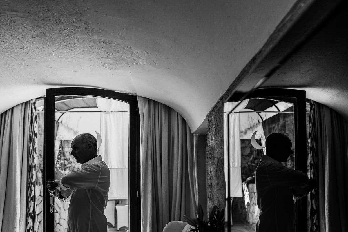 Bräutigam während des Anziehens mit Spiegelung.