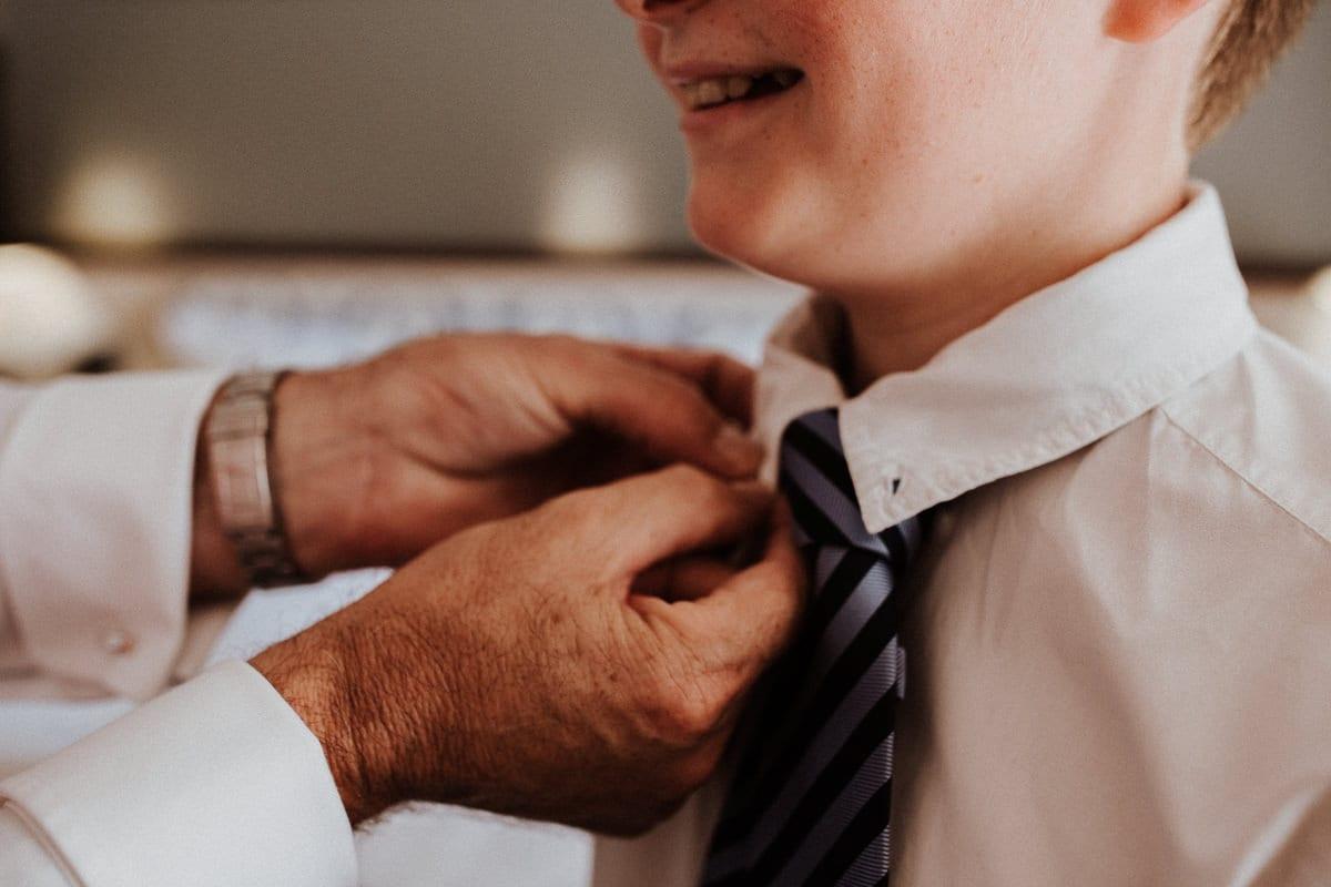 Der Bräutigam richtet die Krawatte seines kleinen Sohnes.