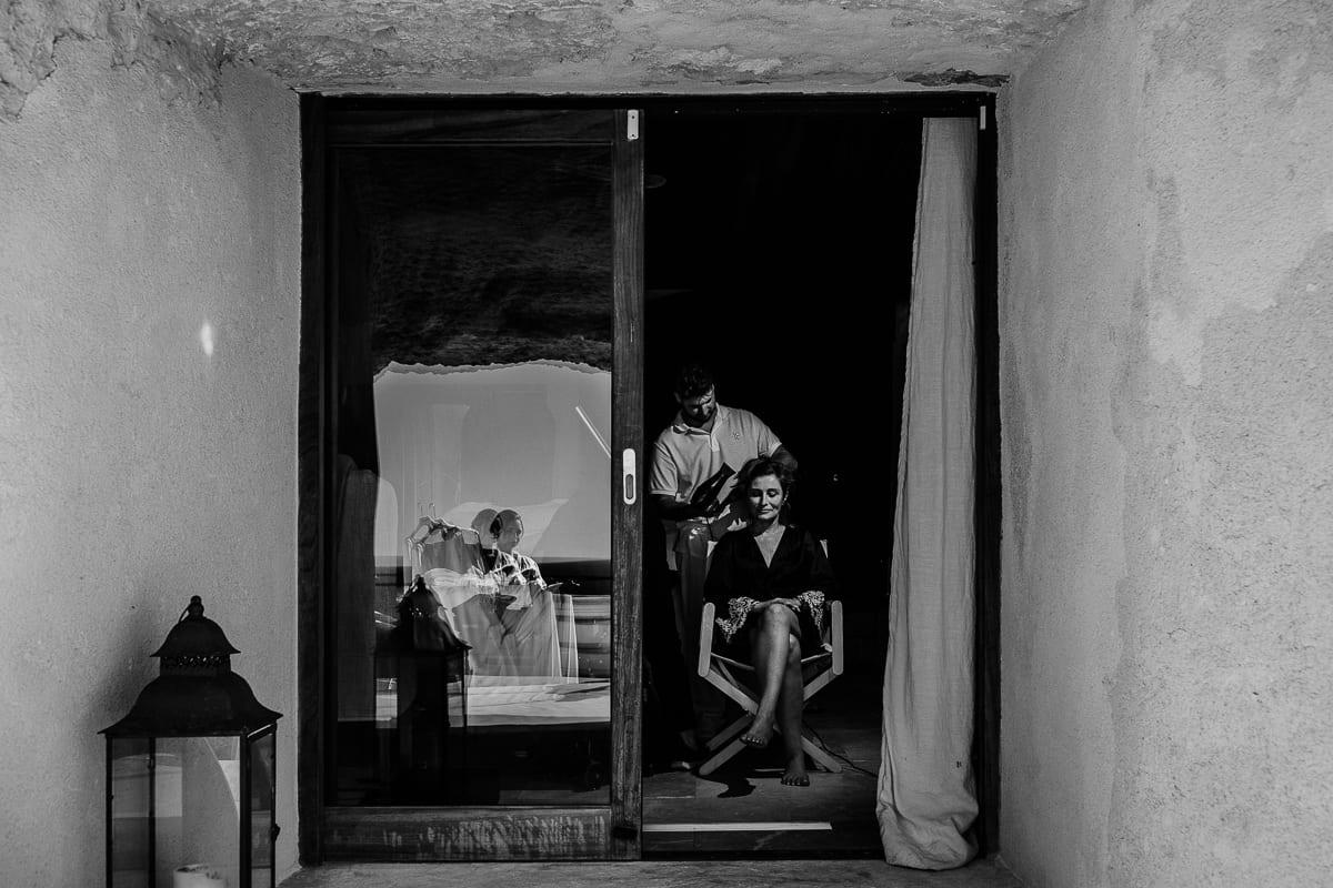 Die Braut wird frisiert. Im Fenster spiegelt sich von draussen die Tochter mit ihrem Brautkleid.
