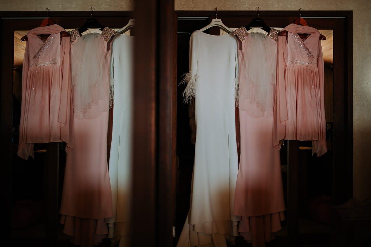 Das Brautkleid und die Kleider aller Mädchen hängend im Zimmer.