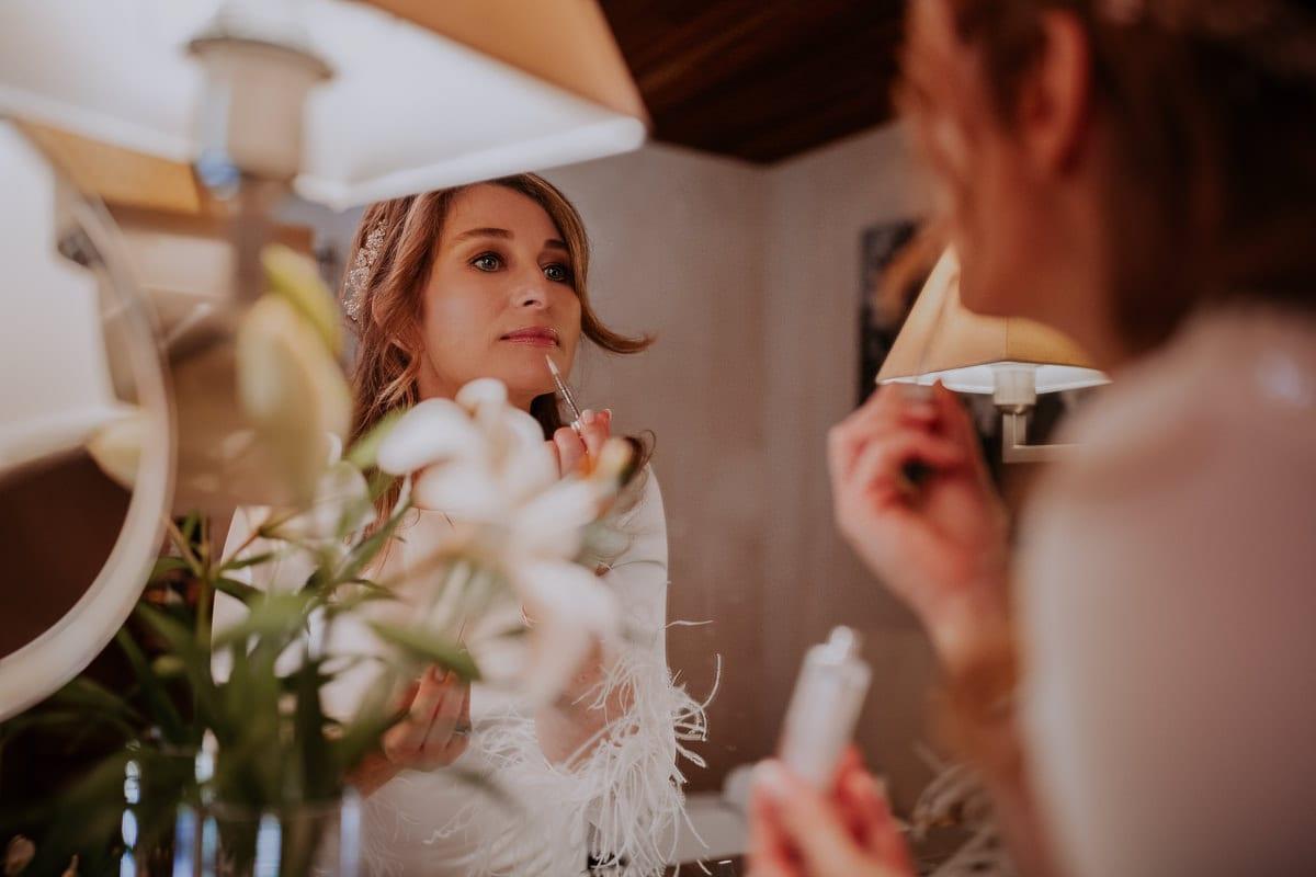Die Braut schminkt ihre Lippen nach.