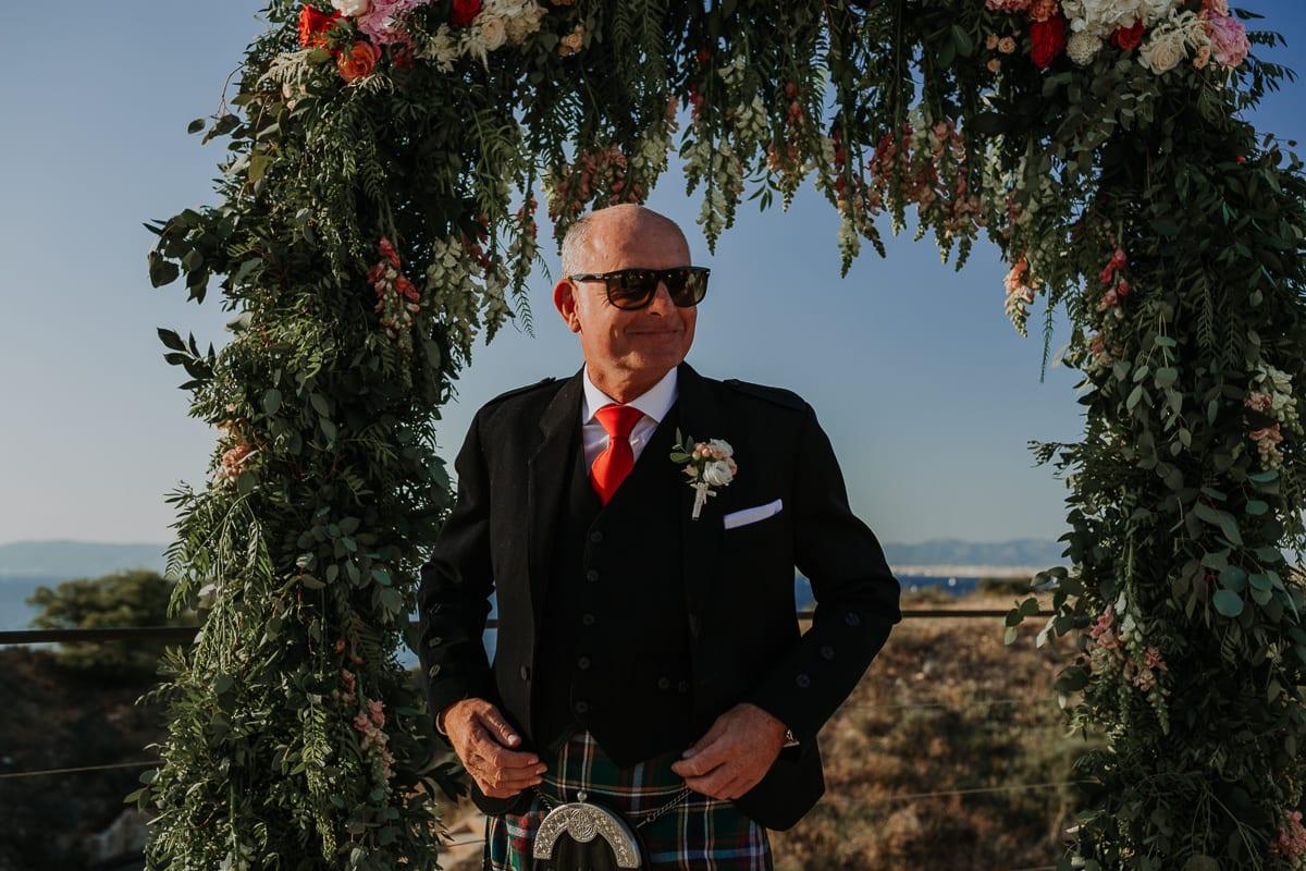 Der Bräutigam wartet unter dem Rosenbogen.