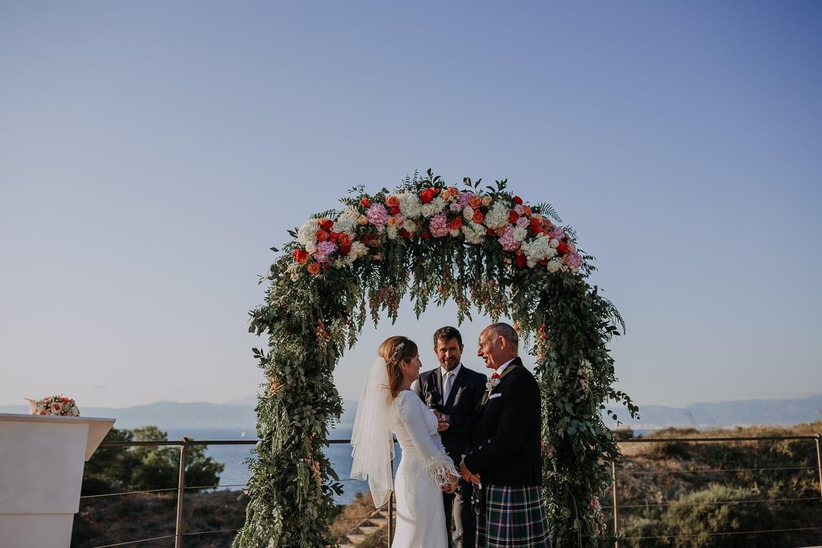 Das Brautpaar und der Hochzeitsredner unterm Rosenbogen.