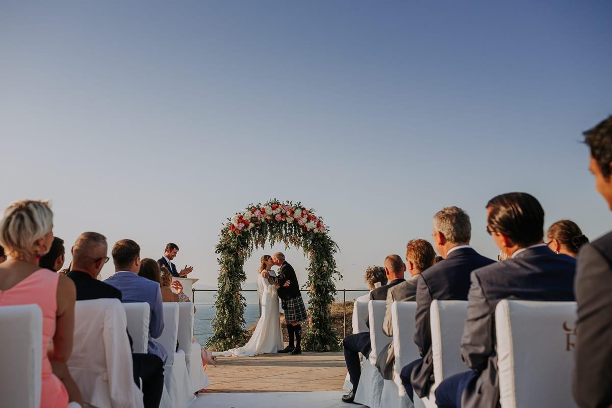 Der Brautkuss unterm Hochzeitsbogen.