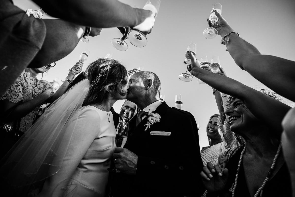 Das Brautpaar küsst sich unter erhobenen Champagner Gläsern.