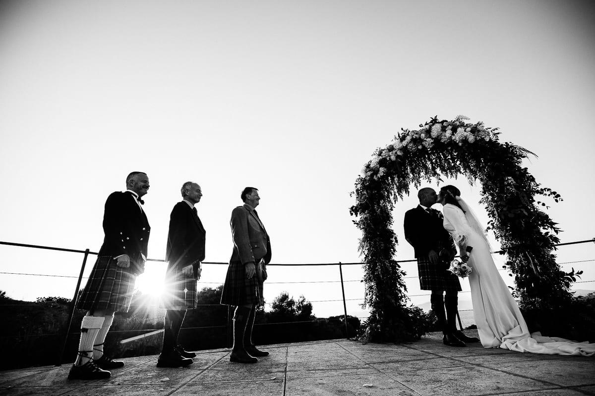 Das Brautpaar küssend unterm Hochzeitsbogen. Die Trauzeugen stehen in schottischer Tracht daneben.