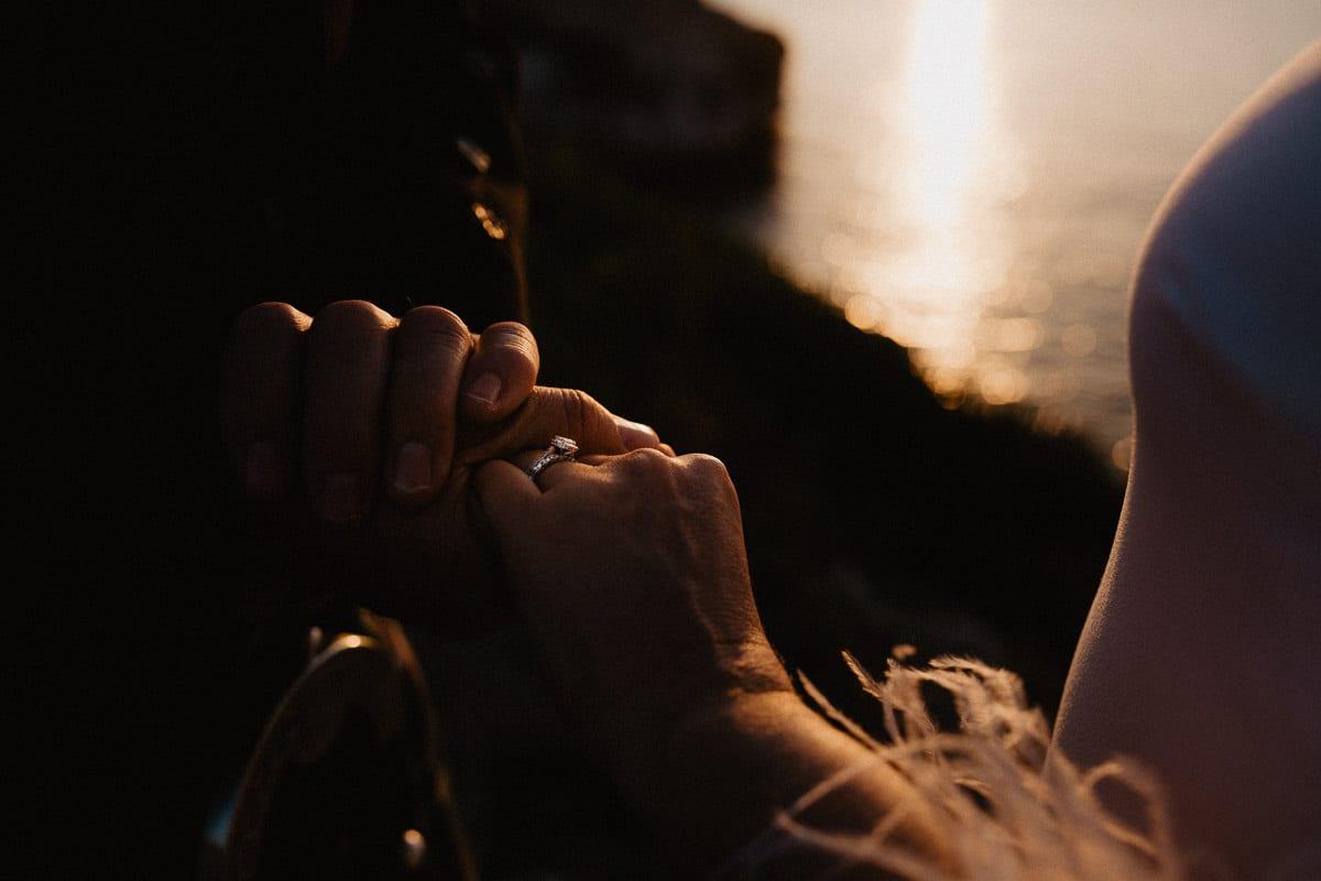 Der Bräutigam hält der Braut die Hände mit dem wunderschönen Ehering an ihrer Hand.
