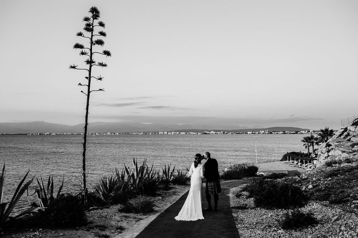Das Brautpaar läuft sich küssend zum Meer.