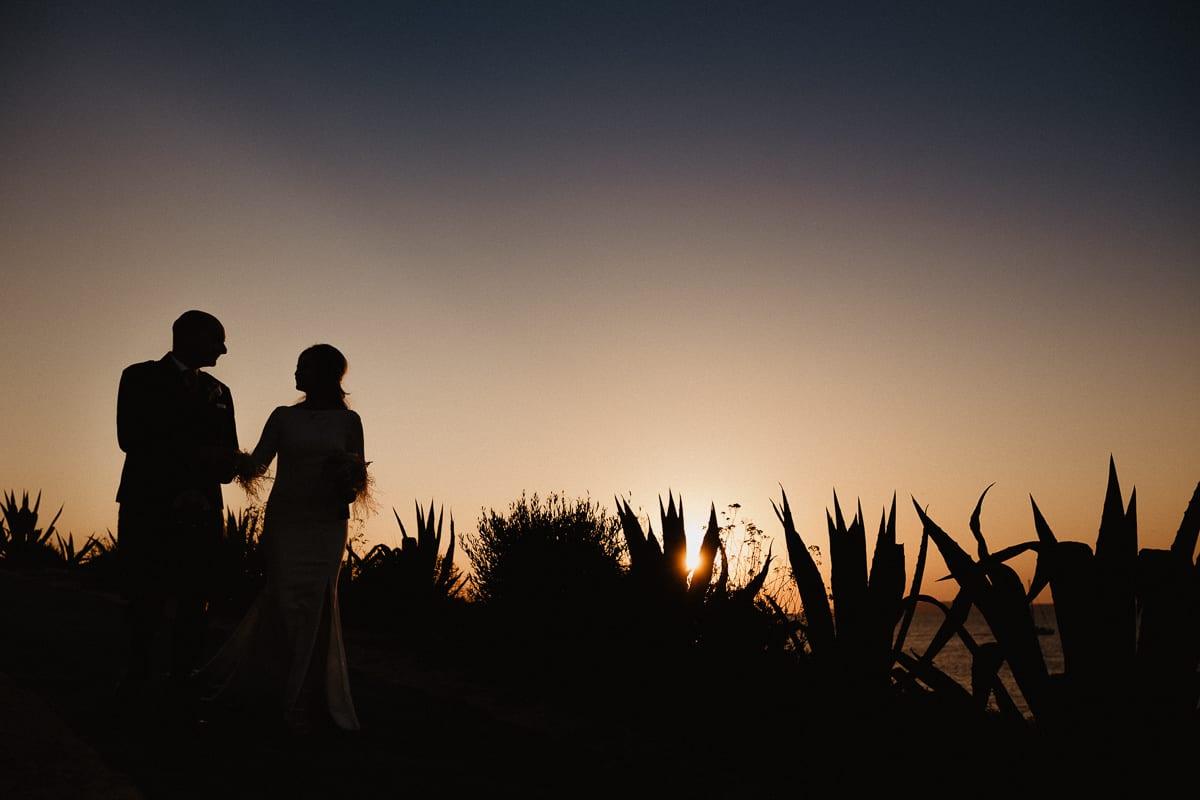 Silhouette des Brautpaares zwischen den Kakteen zum Sonnenuntergang.