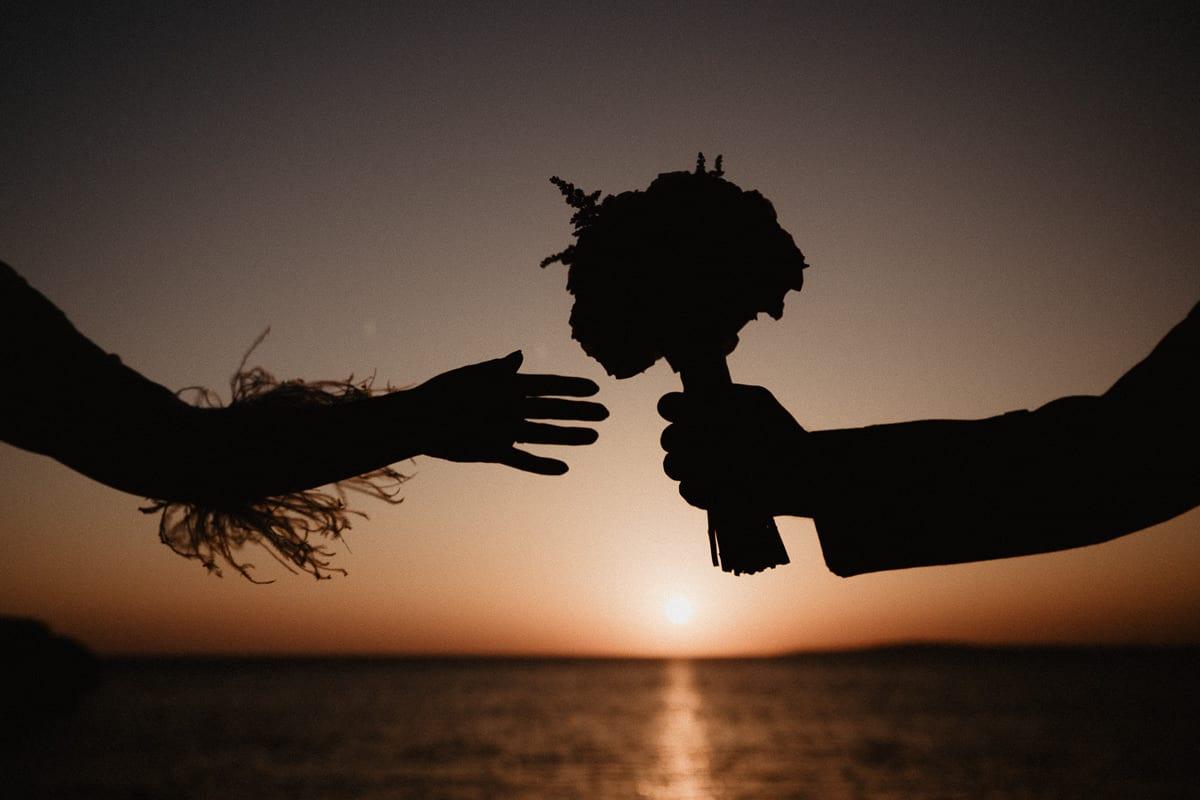 Silhouetten Nahaufnahme des Brautstrausses und der Hände des Brautpaares.
