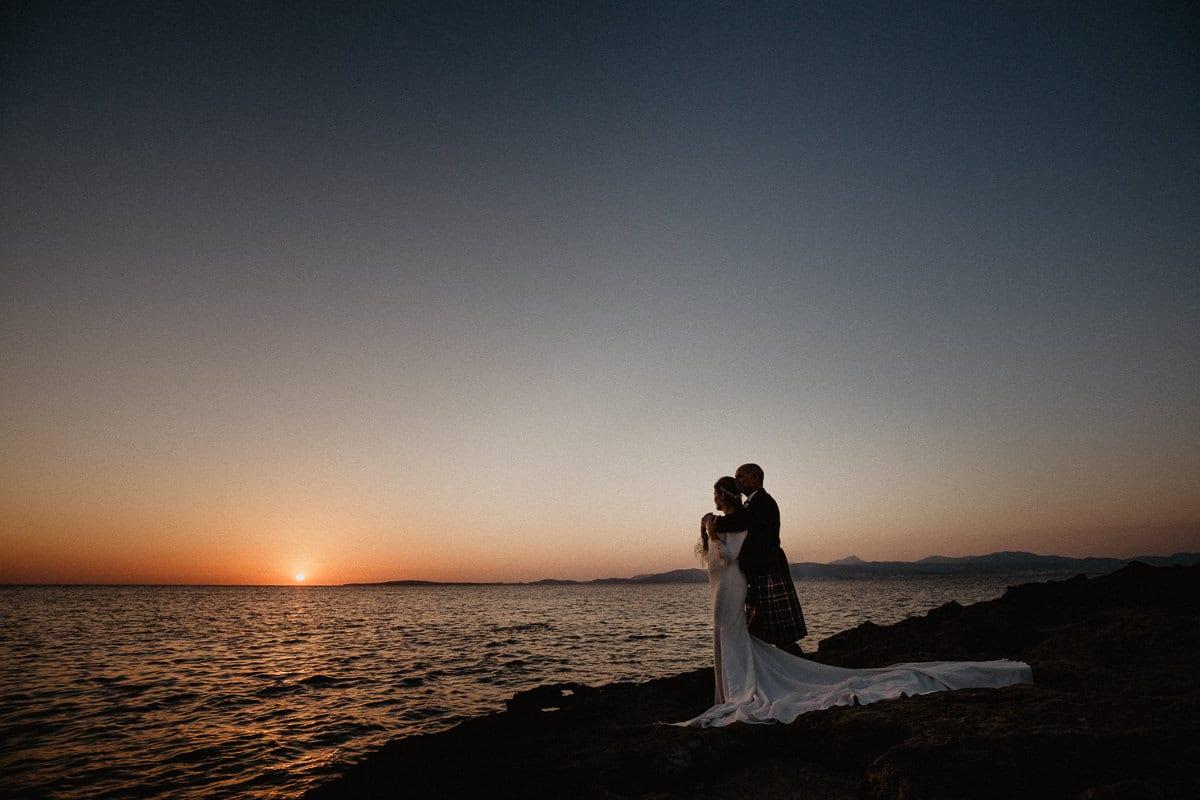 Das Brautpaar geniesst sich umarmend den Sonnenuntergang am Meer.