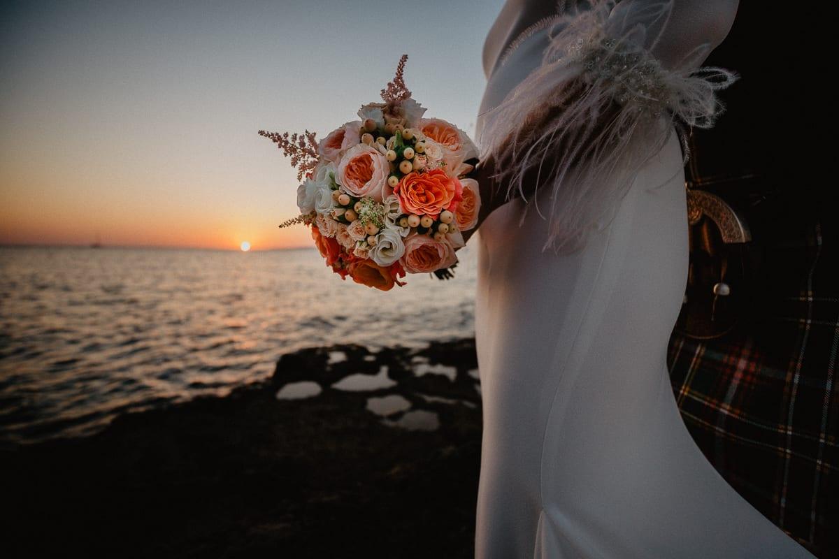 Die Braut hält ihren Brautstrauss zum Sonnenuntergang am Meer.